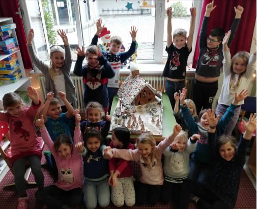 Kinder der Schulkindbetreuung mit einem Lebkuchenhaus